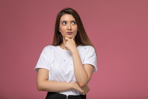 ピンクの壁に思考表現でポーズをとる白いシャツの正面図若い女性、写真色の女性のポーズモデル