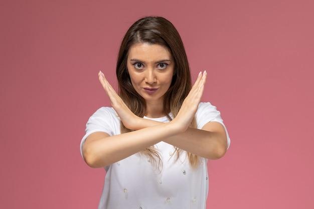 Вид спереди молодая женщина в белой рубашке, показывающая знак запрета на розовой стене, цветная женщина-модель