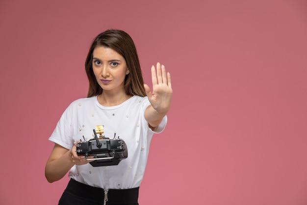 ピンクの壁にリモコンを保持している一時停止の標識を示す白いシャツの正面図若い女性、モデル女性ポーズ女性
