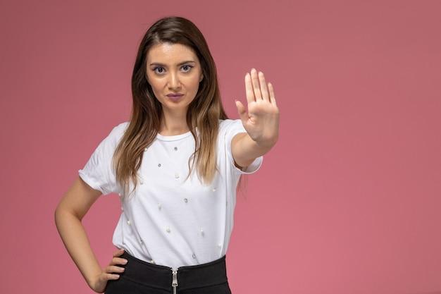 ピンクの壁に一時停止の標識を示す白いシャツの正面図若い女性、モデルの女性のポーズの女性