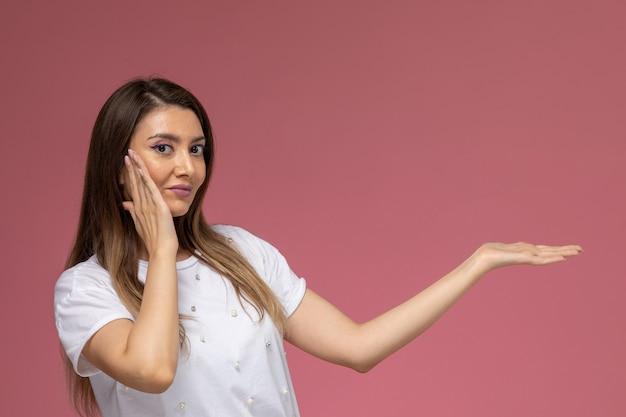ピンクの壁にポーズをとって笑っている白いシャツの正面図若い女性、カラー女性ポーズモデル