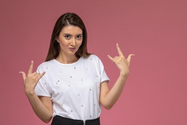 ピンクの壁にポーズをとってロッカーを笑っている白いシャツの正面図若い女性