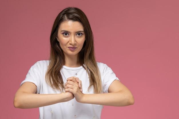 ピンクの壁に拳を握る白いシャツの正面図若い女性、カラー女性ポーズモデル