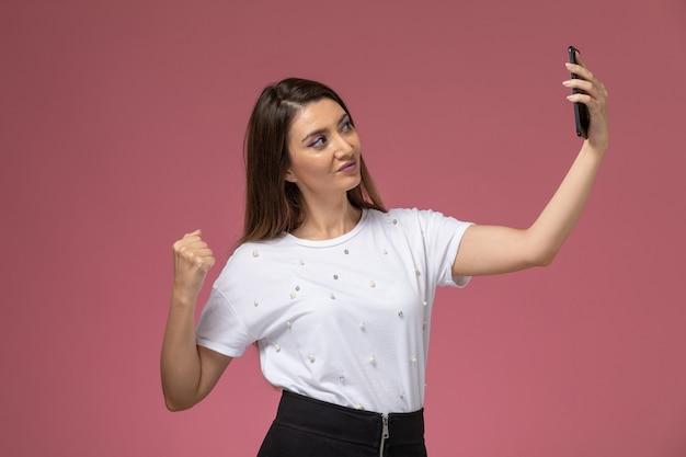 ピンクの壁でselfieを取っている白いシャツの正面図若い女性、モデルの女性のポーズ