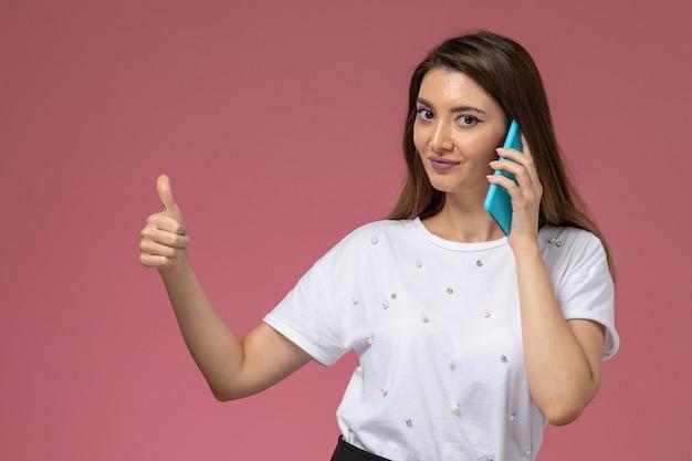 ピンクの壁、色の女性のポーズモデルで電話で話している白いシャツの正面図若い女性