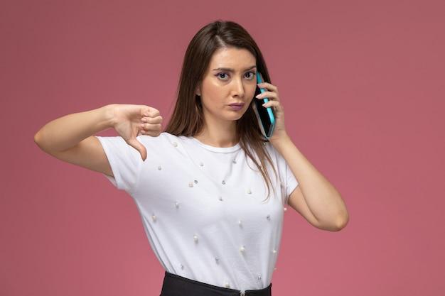 ピンクの壁に電話で話している白いシャツの正面図若い女性、写真の色の女性のポーズモデル