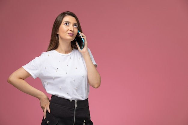 ピンクの壁に電話で話している白いシャツの正面図若い女性、モデルの女性ポーズの女性