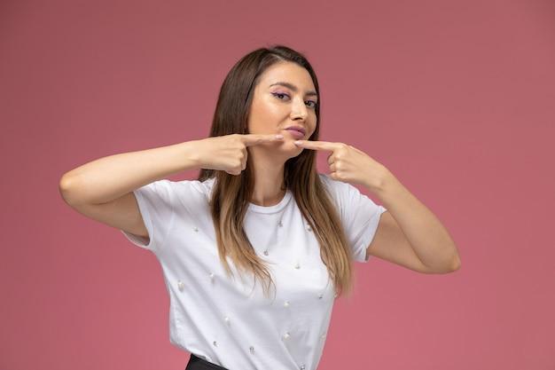 ピンクの壁にニキビに触れる白いシャツの正面図若い女性、カラー女性ポーズモデル