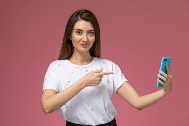 ピンクの壁に彼女の電話を使用して白いシャツを着た若い女性の正面図、カラー女性ポーズモデル女性
