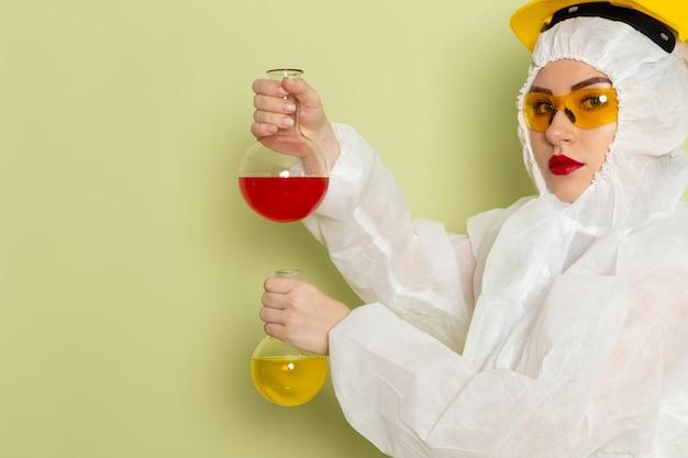 白い特別なスーツと緑のスペースにedソリューションを保持している黄色いヘルメットの正面の若い女性