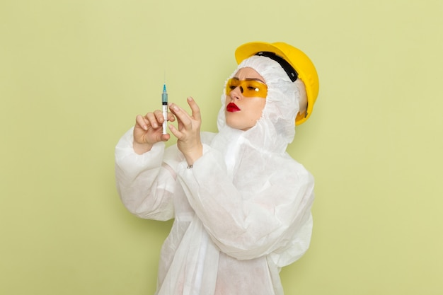 緑の空間化学作業服に注射を保持している白い特別なスーツと黄色いヘルメットの正面若い女性