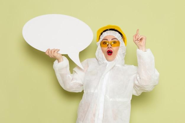 白い特別なスーツと緑の空間化学作業sに大きな白い看板を持っている黄色いヘルメットの正面の若い女性