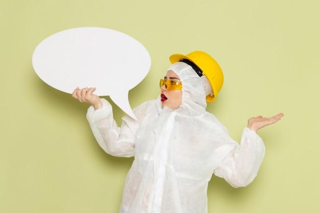 Вид спереди молодая женщина в белом специальном костюме и желтом шлеме держит большой белый знак на зеленых космических костюмах химии