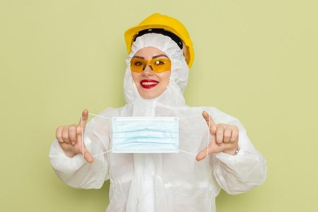 緑の空間化学作業sに少し笑顔で滅菌マスクを保持している白い特別なスーツと黄色いヘルメットの正面の若い女性