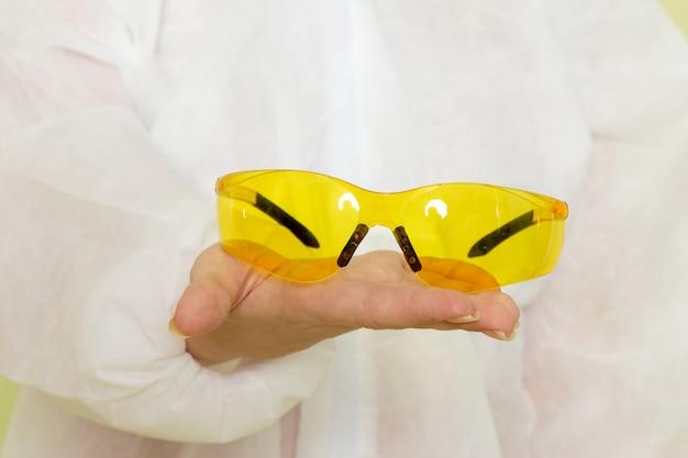 白い特別なスーツと緑のスペースの仕事に黄色の特別なサングラスを保持している黄色のヘルメットの正面の若い女性