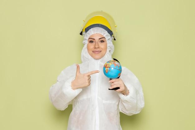 Вид спереди молодая женщина в белом специальном костюме и желтом шлеме, улыбаясь, держит маленькую круглую тарелку на зеленом пространстве