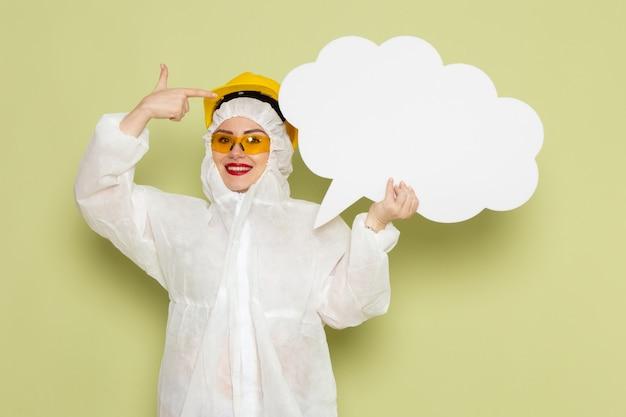 흰색 특수 양복과 녹색 공간 작업에 흰색 거대한 기호를 들고 웃 고 노란색 헬멧에 전면보기 젊은 여성