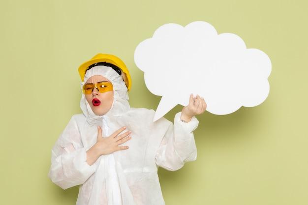 흰색 특수 양복과 녹색 공간에 거대한 흰색 기호를 들고 노란색 보호 헬멧에 전면보기 젊은 여성
