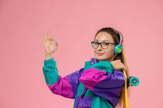 분홍색 배경에 스케이트 보드를 들고 이어폰을 통해 음악을 듣고 흰색 티셔츠 에드 코트에 전면보기 젊은 여성