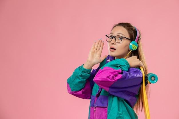 Вид спереди молодая женщина в белой футболке ed пальто слушает музыку через наушники, держа скейтборд на розовом столе