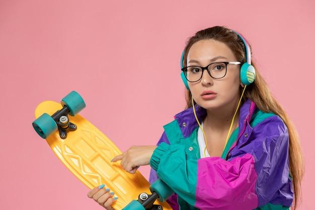 분홍색 배경에 스케이트 보드와 이어폰을 통해 음악을 듣고 흰색 티셔츠 에드 코트에 전면보기 젊은 여성