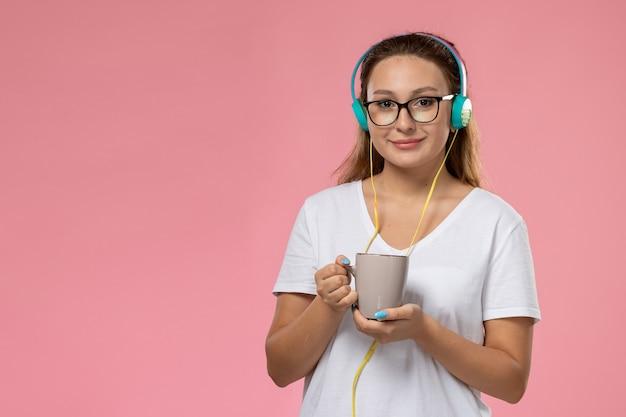 イヤホンを介して音楽を聴くとピンクの背景にお茶とカップを保持している白いtシャツの正面の若い女性