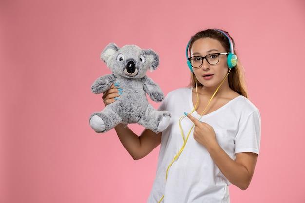 Молодая женщина в белой футболке, вид спереди, просто слушает музыку в наушниках и держит симпатичную игрушку на розовом столе