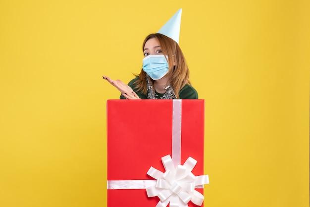 滅菌マスクのプレゼントボックス内の若い女性の正面図
