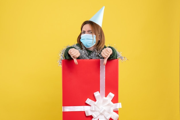 Вид спереди молодой женщины внутри подарочной коробки в стерильной маске