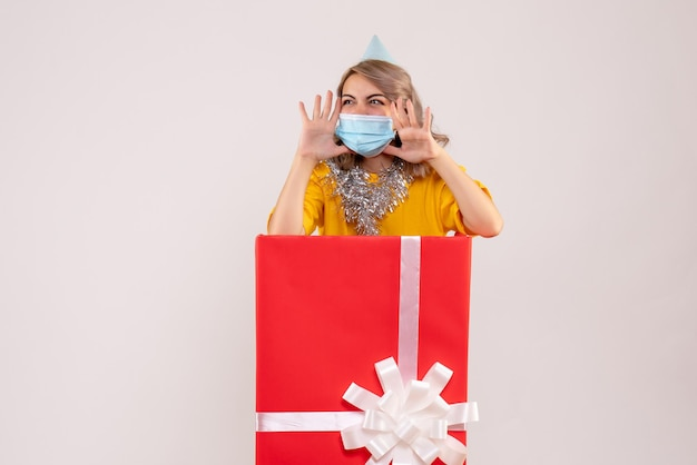 마스크에 빨간색 선물 상자 안에 전면보기 젊은 여성