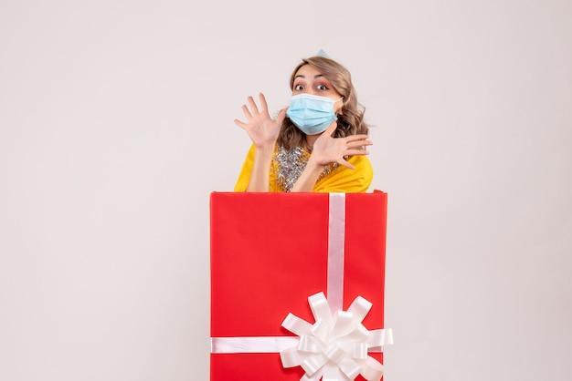 Вид спереди молодая женщина внутри красной настоящей коробки в маске