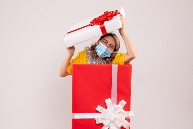 マスクの赤いプレゼントボックス内の若い女性の正面図