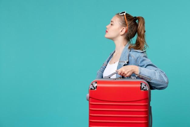 Giovane femmina di vista frontale in giacca di jeans che tiene la sua borsa rossa sullo spazio blu
