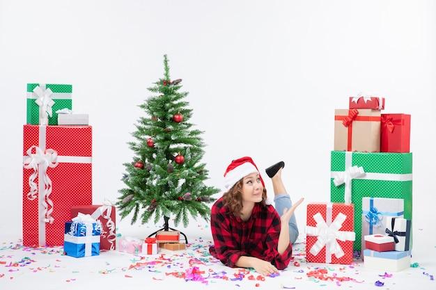 Вид спереди молодая женщина, лежащая вокруг рождественских подарков и маленькой праздничной елки на белом фоне, женщина, цвет, новый год, рождественский снег