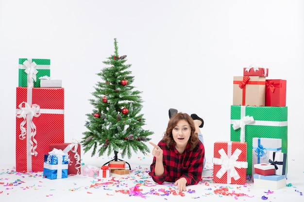 Front view young female laying around christmas presents and holiday tree on white background gift xmas new year color snow