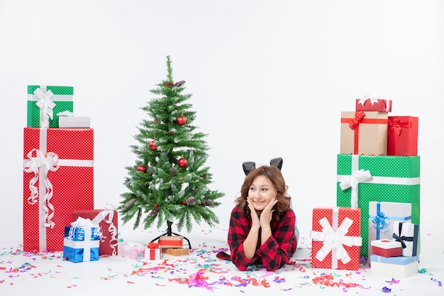 Front view young female laying around christmas presents and holiday tree on white background xmas new year gift colors snow