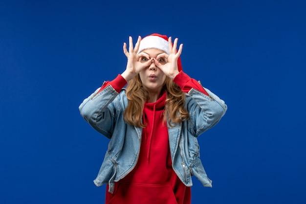 Vista frontale giovane femmina guardando attraverso le dita su sfondo blu natale colore emozione