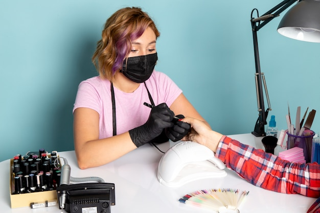 A front view young female manicure in pink t-shirt with black gloves and black mask doing manicure on blue