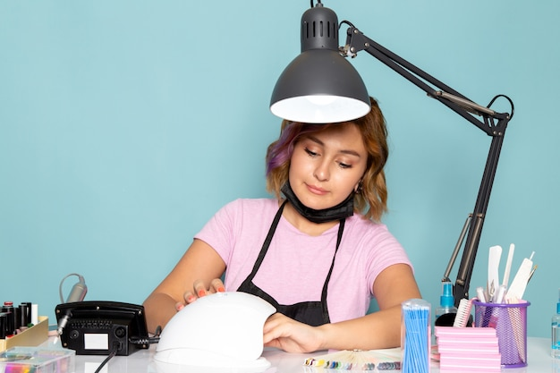 Una giovane donna manicure vista frontale in maglietta rosa con guanti neri seduto davanti al tavolo a lavorare con le unghie sull'azzurro