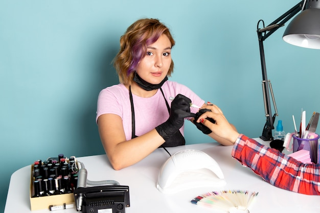 A front view young female manicure with black gloves and black mask doing manicure on blue