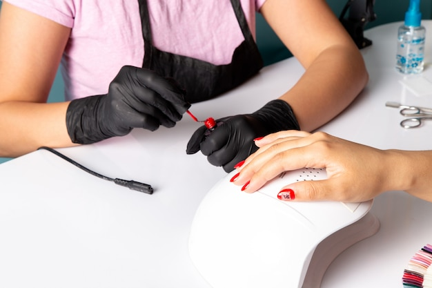 A front view young female manicure with black gloves doing manicure on white