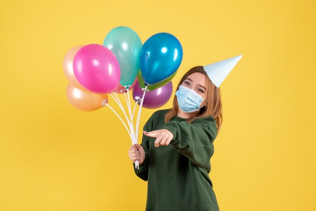 Giovane donna di vista frontale in maschera che tiene palloncini colorati