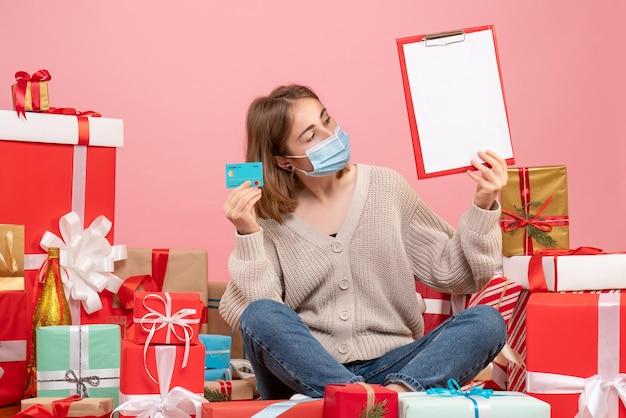 Giovane femmina di vista frontale nella maschera che si siede intorno ai regali di natale