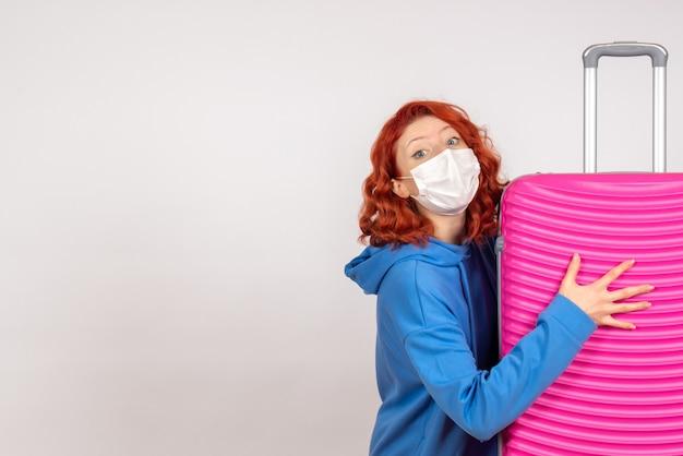 Vista frontale della giovane donna in maschera con la sua borsa rosa sul muro bianco