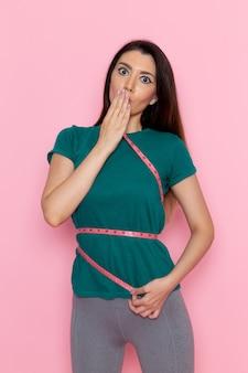 Вид спереди молодой женщины, измеряющей свои размеры на светло-розовой стене, упражнения, спорт, тренировка, талия, красота