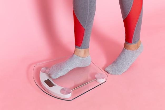 ピンクの壁のエクササイズスポーツトレーニングアスリートウエストの美しさで彼女の体重を測定する正面図若い女性