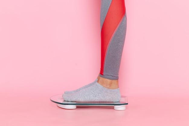 ピンクの壁のウエストスポーツ運動トレーニング美容スリムアスリートで彼女の体重を測定する正面図若い女性