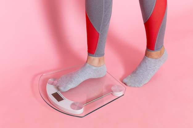 Front view young female measuring her weight on pink wall exercise sport workout athlete waist beauty