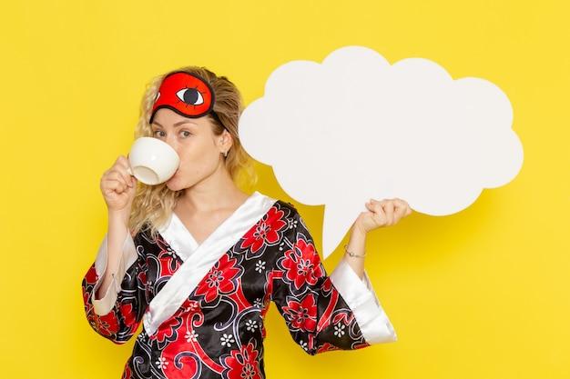 Vista frontale giovane femmina in abito da notte con un enorme cartello bianco e bere caffè sul muro giallo dormire notte letto modello colore