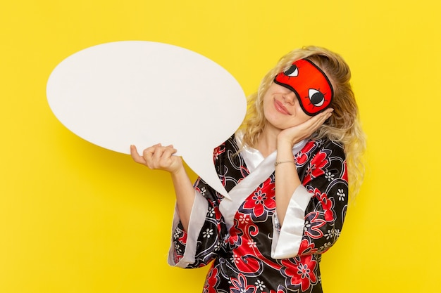 Giovane donna di vista frontale in abito da notte che tiene un enorme segno bianco sul colore della ragazza del modello di letto di notte di sonno di colore giallo chiaro